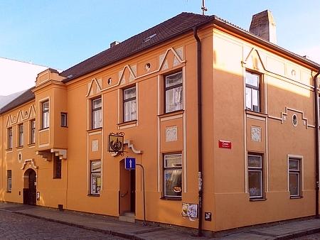"""Dům čp. 11 v Piaristické ulici, zvaný """"U Černé růže"""", nesl původně jméno """"Zum schwarzen Rössl"""", tj. """"UČerného koníčka"""",     a byl v něm měšťanský pivovar, svého času také, jak vidno z hořejší pohlednice, ta """"největší a nejkrásnější kavárna ve městě"""""""