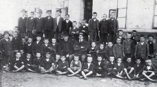 Pan učitel Lad se žáky v Kaltenbachu, vedle něho sedí farář Zoubek