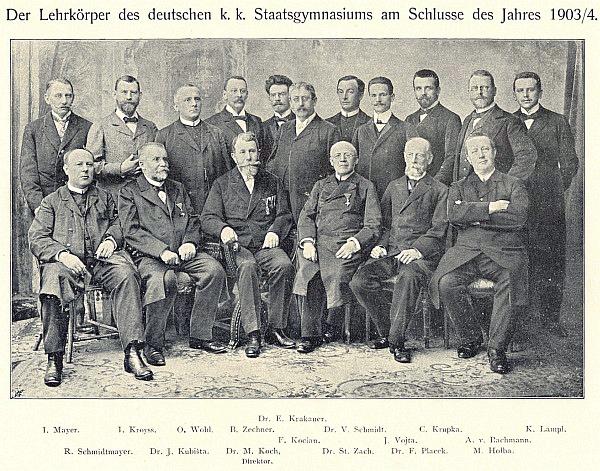 """Stojící prvý zprava na snímku učitelského sboru německého gymnázia na závěr školního roku 1903/1904- čtvrtý zprava stojí tu ještě s jednoduchým """"V"""" psaný Johann Wojta, pátý vedle něho Valentin Schmidt a prvý zleva sedí Rudolf Schmidtmayer, vprostřed pak třetí zleva sedí  Mathias Koch a třetí zprava  Stephan Zach"""