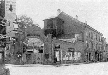 Další jím pořízený snímek dokumentuje zástavbu rohu Biskupské a Radniční ulice s branou hasičské stanice, stržené v roce 1928 a nahrazené palácem pojišťovny Fénix