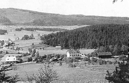 Vlevo při cestě k nádraží v Lenoře je vidět zářivou střechu domu, který si postavil v letech 1925-1926, v pozadí osada Houžná a vrch Chlustov