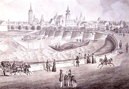 Říční bagr tu už někdy v půli 19. století čistí dno Vltavy při Dlouhém mostě na vedutě města České Budějovice, pořízené přibližně od Lannova rodného domu