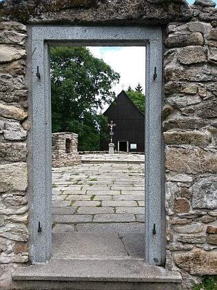 Základy kostela a opravená hřbitovní kaple Svatého kříže v Hůrce