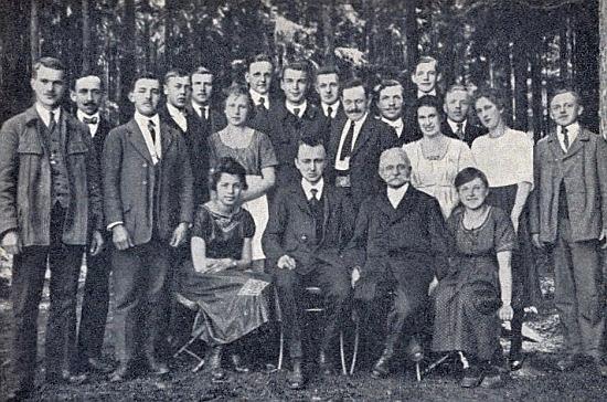 """Sedí tu uprostřed vedle Hanse Schreibera na učebním kurzu tzv. """"Volkshochschule"""", tj. """"lidové univerzity"""" vLázních sv. Markéty u Prachatic roku 1921 zachycen fotografií, doprovázející pamětnický text JosefaBerause o této akci"""