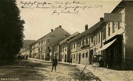 Tady je rodný dům zachycen na pohlednici Josefa Wolfa vpravo od chlapce stojícího uprostředulice