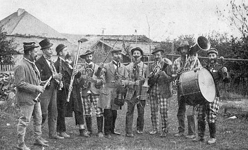Na dvoře volarské měšťanky někdy v roce 1914 stojí se zdviženým smyčcem uprostřed členů volarského pěveckého souboru
