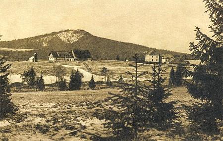 Rodná Horská Kvilda na staré pohlednici vpravo s Pollaufovým hostincem a školou, vzadu vrch Sokol