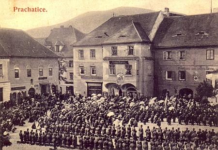 Stará pohlednice Prachatic zachycuje polní mši na Velkém náměstí roku 1915 před domem,     v němž je dnes umístěna Galerie Otto Herberta Hajeka
