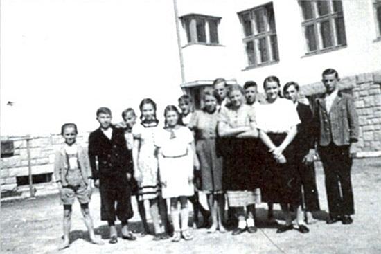 Ve školním roce 1938/1939 tu stojí Wally Klingerová čtvrtá odleva se svými spolužáky před měšťanskou školou v tehdejším Německém Benešově