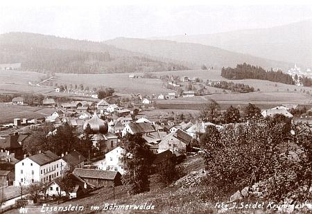Na této pohlednici českokrumlovské firmy Josef Seidel vidíme od Železné Rudy vpravo vzadu i Bavorskou Železnou Rudu s vysokou kostelní věží