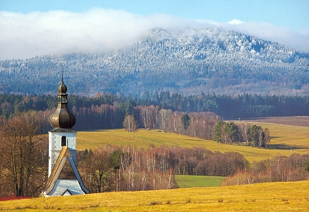 Věž kostela sv. Jiljí v Rychnově u Nových Hradů s ojíněným Vysokým Kamenem (Slepicí) za ní