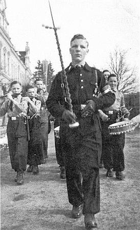 """Tady kráčí Sepp Matejka v čele chvalšinské Hitlerjugend krátce po záboru pohraničních území téměř jako """"krysař zHameln"""", za nimi fasáda místní školy"""