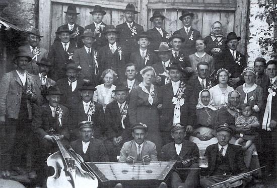 """""""Chrobolder Zimbalmusi"""" sedící vepředu jako doprovod jedné venkovské svatby - první zleva s kontrabasem Thomas Mertl otec"""