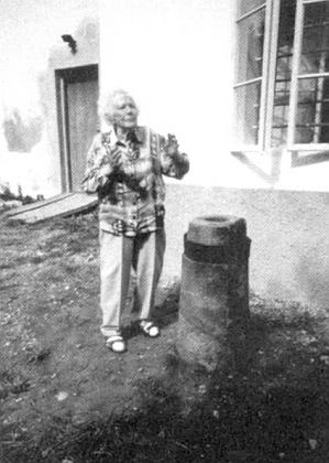Nejstarší německá krajanka z někdejší Šenavy paní Julia Gabrielová (Sogotum) nasnímku s kamenným sloupkem namilodary (Opferstock), patřícímu kdysi ke kapli na Červeném vrchu a stojícímu nyní na zahradě fary vdnešní Pěkné