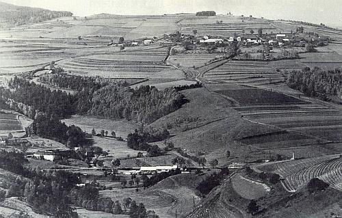Pohled zachycující dole vpředu jeho rodnou ves Branná (Pramles) uprostřed s někdejším hamrem, nahoře vpravo nad ní pak Nahořany (Hochdorf)