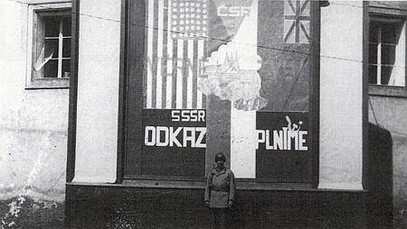 """Snímek, zachycující vzhled někdejší propagační tabule """"NS-Kreisleitung"""" při Červené bráně do českokrumlovského zámku (za ní se Multererův úřad nacházel) a podivnou vlajkoslávou , siluetou Hradčan a poprsím Edvarda Beneše, ten voják na stráži je asi Američan"""