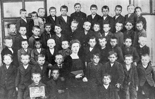 """Mezi spolužáky ročníků narození 1912-1914 v rodném Kaltenbachu s paní učitelkou Travnitschek-Juglovou je tu zachycen ve druhé řadě třetí zprava, v poslední řadě nahoře třetí zleva lesníkův """"Gustl"""" Hoke"""