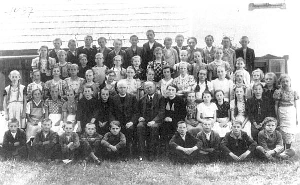 Paní učitelka Fremuthová s farářem Neuwirthem a křišťanovskými dětmi na snímku z roku 1937