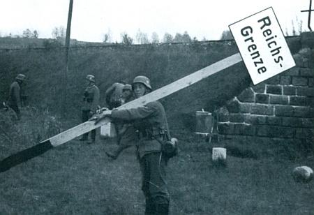 """Na tomto snímku z nacistické propagační publikace nese v září 1938 """"říšský voják"""" při náspu železniční trati vNovém Údolí hraniční tabuli, která """"se musí přesunout do vnitrozemí"""""""