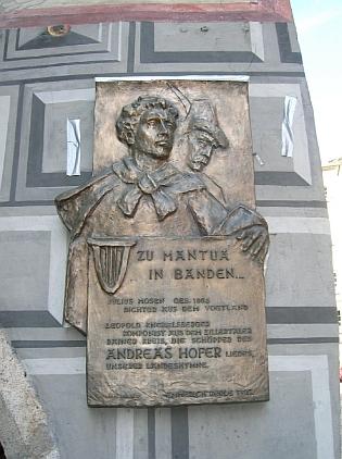 """Pamětní deska na fasádě hotelu """"Goldener Adler"""" v tyrolském Innsbrucku připomíná autora textu písně """"Zu Mantua in Banden"""", od roku 1948 tyrolské hymny, jímž byl Julius Mosen z Vogtska (Vogtland), hudbu složil Leopold Knebelsberger z Klosterneuburgu na lidový nápěv"""