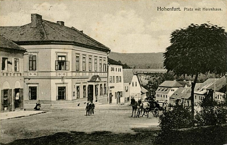 """Na pohlednici Josefa Seidela z téhož roku 1921 je rodný dům zachycen vpravo od """"Panského domu"""", který dominuje této části náměstí"""