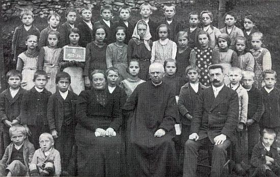 Pan učitel Fuger tu ve školním roce 1923/1924 sedí v první řadě vpravo vedle učitele náboženství Gustava Praxla,     učitelky ručních prací Hermine Groissové a žáků hornovltavické obecné školy