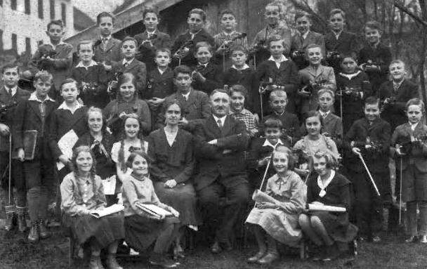 Jedenáctiletá Gertrud Kramlová sedící první zleva mezi žáky hudební školy ve Volarech vepředu uprostřed s panem ředitelem Wolfgangem Oberhoferem