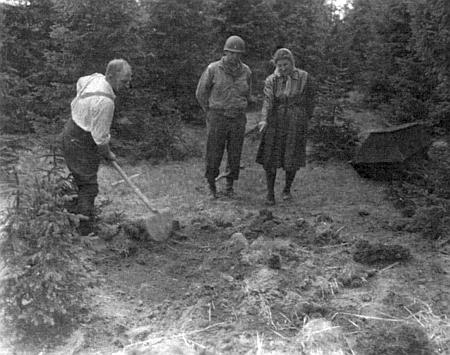 Jeden volarský civilista s lopatou na počátku exhumace těl židovských žen z pochodu smrti ve Volarech za dohledu židovského duchovního US Army Hermana Dickera a nejstarší z těch, které pochod přežily, tj. Miny Singerové - snímek byl pořízen 11. května roku 1945