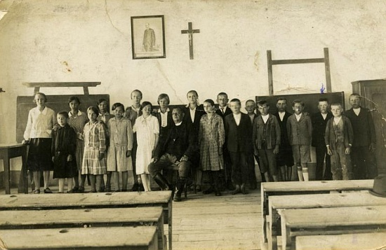 Jedna z tříd školy v Cetvinách mezi válkami s farářem Františkem Havlem, rodákem z Novosedel nad Nežárkou, pod obrazem prezidenta Masaryka a křížem