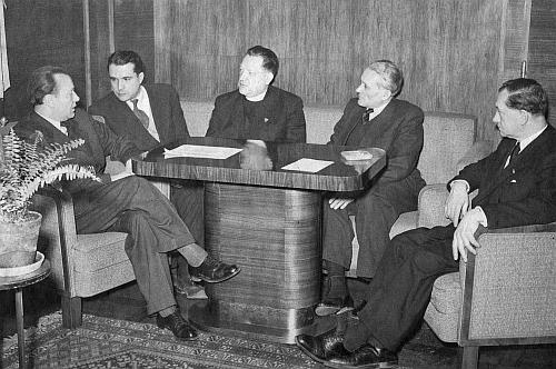 Dva dny po 25. únoru roku 1948 sedí tu odleva Gottwaldův zeť Alexej Čepička, francouzský komunistický novinář a spisovatel Pierre Courtade, Josef Plojhar, dále redaktor Rudého práva André Simone, odsouzený k smrti v procesu sRudolfem Slánským v roce 1952 a konečně ministr dopravy Alois Petr (1889-1951), který byl stejně jako Plojhar vyloučen z Československé strany lidové už 24. února 1948, oba však s bezpečnostními složkami obsazovali den nato tiskové závody a sekretariát lidové strany