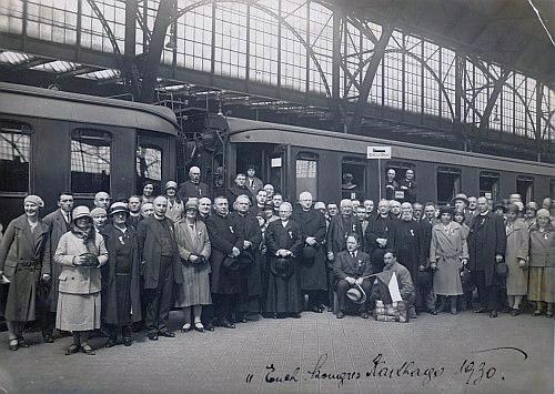 Snímek z pražského Wilsonova nádraží před odjezdem na kongres v Kartágu zachycuje tehdy osmadvacetiletého Plojhara v kolárku uprostřed celé skupiny přímo při dveřích vagonu