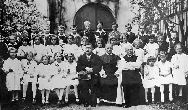 Na smímku z prvního svatého přijímání v Rožmberku nad Vltavou z roku 1925 sedí uprostřed mezi řídícím učitelem Brabetzem a katechetou Blöchlem