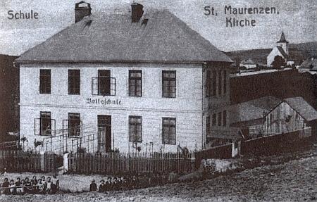 Škola v Mouřenci, kde také učil, na staré pohlednici, v pozadí starobylý kostel sv.Mořice, který dal osadě jméno