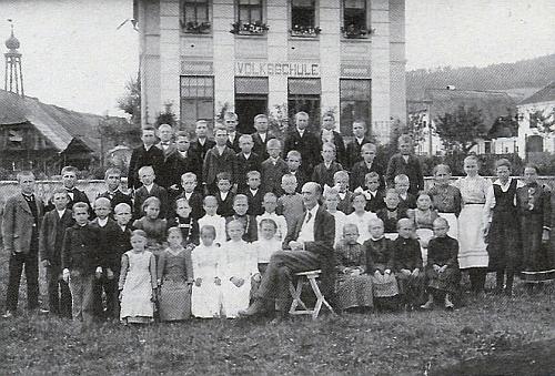 Škola v Borové na snímku Josefa Seidela z roku 1920 tu tvoří kulisu snímku učitele a dětí