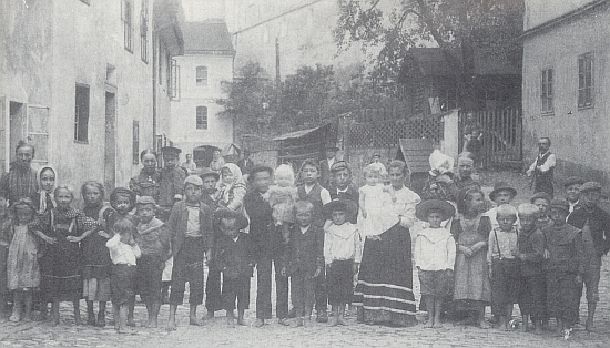 Děti na českokrumlovském Parkáně v létě 1920, tři roky předtím, než se v září 1923 Posner v domě vepředu nalevo narodil...
