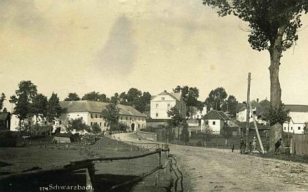 Stará pohlednice Černé v Pošumaví z fotoateliéru Josefa Wolfa zachycuje část obce u cesty na Český Krumlov - Proschkův rodný dům čp. 23 stál při ní o něco výše, na snímku vidět není