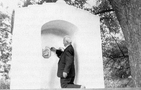To on sám tu klečící zavěšuje obrázek do obnovené kaple v zaniklém Lověšickém Rovném