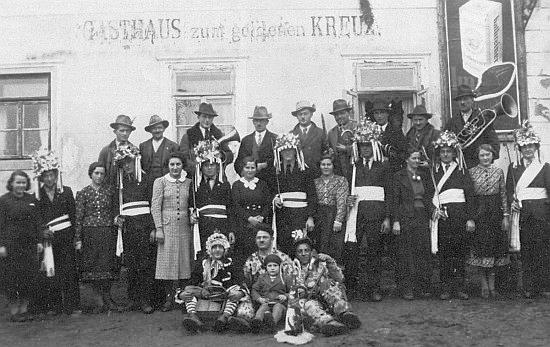 """Tady je tehdy osmnáctiletá Katharina Klementová zachycena před hostincem """"Zum goldenen Kreuz"""" druhá zprava v první řadě v lednu 1939, kdy ve vsi ožívaly """"mečové tance"""""""