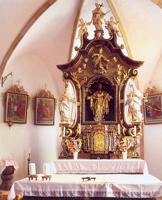 Hlavní oltář malšínského kostela Srdce Ježíšova (původně sv. Markéty) se sochami sv.Barbory aKateřiny po stranách, nahoře se sv.Janem Nepomuckým mezi dvěma anděly