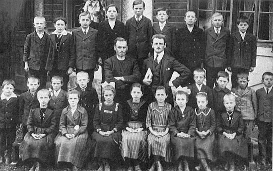 Pan učitel Raab s farářem Valentou a se žáky školy v Nižších Hodonicích (Hodenitz) na snímku z roku 1922