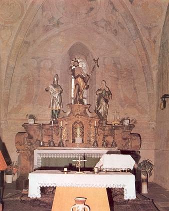 Oltář kostela v Janovicích nad Úhlavou s dřevěnými sochami sv. Jana Křtitele, sv. Alžběty asv. Zachariáše agotickými freskami v pozadí na Raischově snímku