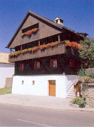 """Dům Regnerových v Rittsteigu, jehož současní majitelé, rodina Lembergerova, byli v roce 1991 vyznamenáni za """"s krajinou spjatý vzhled stavby"""""""