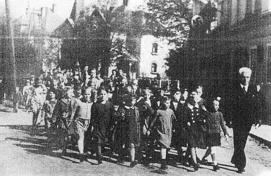 Pan učitel August Rehder mladší vede v Nýrsku děti k prvomájové oslavě roku 1939