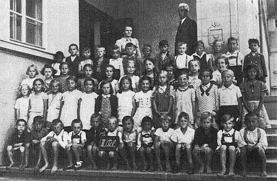 Týž před budovou po připojení k Říši zabrané české školy v Nýrsku, u níž byl spálen její školní archiv a české školní knihy