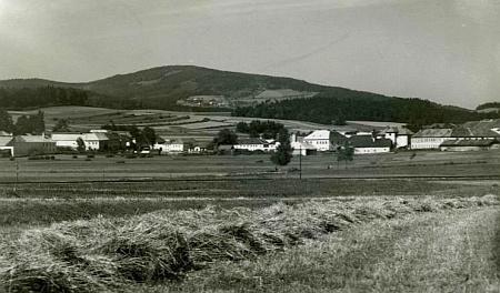 Rodná Hůrka od jihu se železniční tratí vpředu a obilným polem už v místech dnešního Lipenského jezera