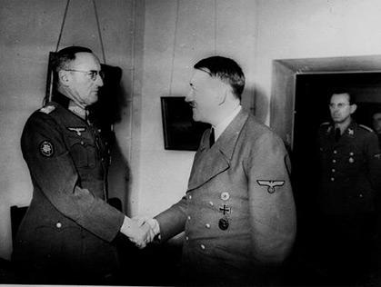 Jedna z posledních fotografií Adolfa Hitlera z roku 1945 v jeho berlínském bunkru při stisku ruky s gen. Ferdinandem Schörnerem, jmenovaným ve vůdcově poslední vůli azávěti vrchním velitelem neexistujícího už wehrmachtu - vedveřích stojí Hitlerův adjutant Julius Schaub