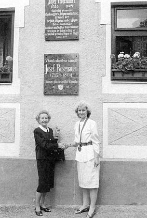 U pamětních desek na jeho rodném domě vidíme starostku Chvalšin Vlastu Novákovou při stisku ruky sčestným hostem slavnosti kjejich odhalení paní Charlotte Rosenauerovou, vdovou oslavencova prapravnuka