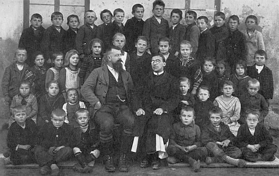 Se žáky první třídy školy v dnes zaniklém Kyselově v roce 1924 sedí vedle řídícího Rundensteinera farář Lonsing