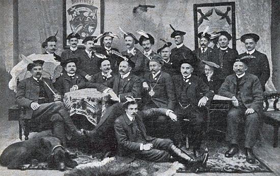 """Na dvou snímcích žertovného sdružení """"Krohwinklia"""" z let 1909 a 1913 (na horním sedí třetí zleva,     na spodním v řadě sedících uprostředustoluskostkovaným ubrusem)"""