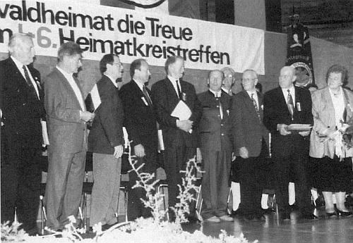 """Na setkání pod názvem """"46. Heimatkreistreffen"""" 50 let po vyhnání 1996 stojí v prvé řadě čtvrtý zprava, uprostřed pátý zleva Richard Schiefer, prvý zleva F. X. Jedlitschka"""